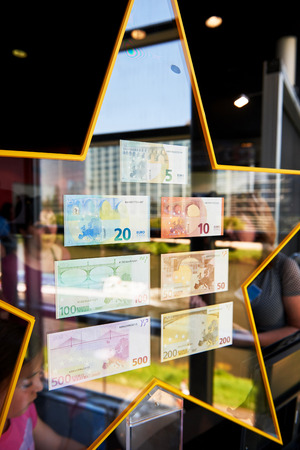 euro notes: STRASBOURG, FRANCE - MAY 8, 2016: Crowd admiring all European Union Euro notes with a beautiful reflection of the window and European Parliament in the stars holding them Editorial