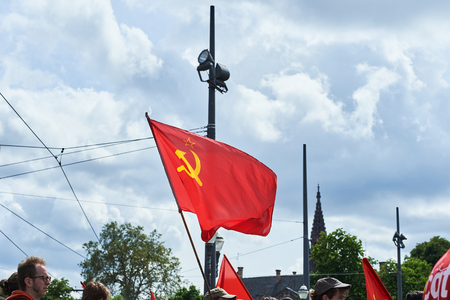 conflictos sociales: STRASBOURG, FRANCE - MAY 19, 2016: Soviet communist flag waving during a demonstrations against proposed French governments labor and employment law reform