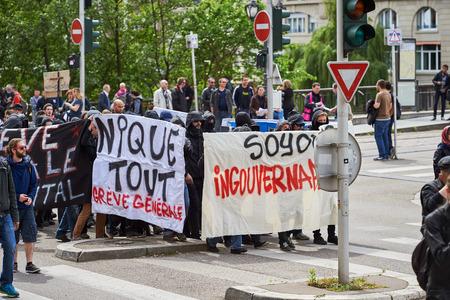 social conflicts: Estrasburgo, Francia - 19 de mayo, 2016: Grupo de personas que youg con el rostro cubierto con pancartas a pie con una multitud durante las manifestaciones contra la reforma del derecho laboral y de empleo propuesta del gobierno franc�s