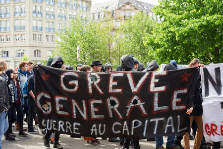 conflictos sociales: STRASBOURG, FRANCE - MAY 19, 2016: Group of youg people with covered faces holding placards walk with crowd during a demonstrations against proposed French governments labor and employment law reform