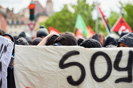 social conflicts: STRASBOURG, FRANCE - MAY 19, 2016: Group of youg people with covered faces holding placards walk with crowd during a demonstrations against proposed French governments labor and employment law reform