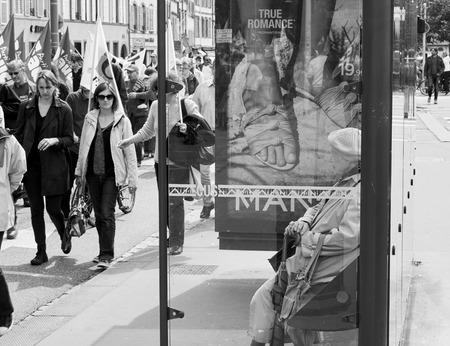 social conflicts: Estrasburgo, Francia - 19 de mayo, 2016: Mujer mayor que mira a los manifestantes que marchan en la calle cerrada durante unas manifestaciones contra la reforma del derecho laboral y de empleo propuesta del gobierno franc�s