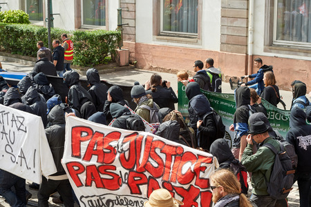 labor union: STRASBOURG, FRANCE - MAY 19, 2016: Group of young people with covered faces holding placards walk with crowd during a demonstrations against proposed French governments labor and employment law reform