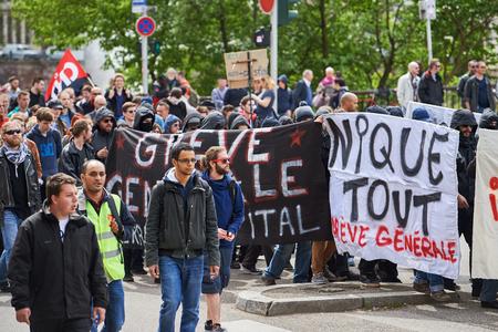 conflictos sociales: Estrasburgo, Francia - 19 de mayo, 2016: Grupo de personas que youg con el rostro cubierto con pancartas a pie con una multitud durante las manifestaciones contra la reforma del derecho laboral y de empleo propuesta del gobierno franc�s