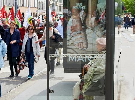 conflictos sociales: Estrasburgo, Francia - 19 de mayo, 2016: Mujer mayor que mira a los manifestantes que marchan en la calle cerrada durante unas manifestaciones contra la reforma del derecho laboral y de empleo propuesta del gobierno francés