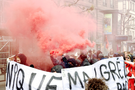 proposed: STRASBOURG, FRANCE - MAY 19, 2016: GRoup with covered faces and smoke grenades throwing paint towards Banque de France building during a demonstrations against proposed French governments labor and employment law reform