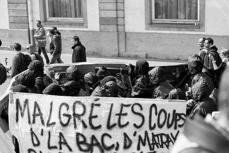 conflictos sociales: Estrasburgo, Francia - 19 de mayo, 2016: Grupo de j�venes con el rostro cubierto con pancartas a pie con una multitud durante las manifestaciones contra la reforma del derecho laboral y de empleo propuesta del gobierno franc�s
