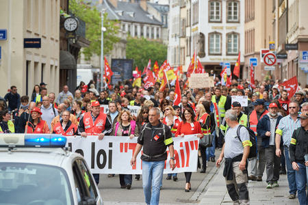 social conflicts: STRASBOURG, FRANCE - MAY 19, 2016: People marching on closed central streets in Strasbourg woth retire labor reform placard during a demonstration against proposed French governments labor and employment law reform