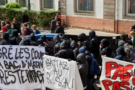 social conflicts: Estrasburgo, Francia - 19 de mayo, 2016: Grupo de j�venes con el rostro cubierto con pancartas a pie con una multitud durante las manifestaciones contra la reforma del derecho laboral y de empleo propuesta del gobierno franc�s