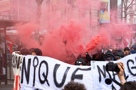 demonstrations: STRASBOURG, FRANCE - MAY 19, 2016: GRoup with covered faces and smoke grenades throwing paint towards Banque de France building during a demonstrations against proposed French governments labor and employment law reform