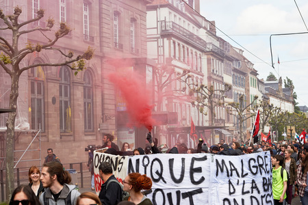 labor union: STRASBOURG, FRANCE - MAY 19, 2016: GRoup with covered faces and smoke grenades throwing paint towards Banque de France building during a demonstrations against proposed French governments labor and employment law reform