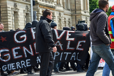 demonstrations: STRASBOURG, FRANCE - MAY 19, 2016: Group of young people with covered faces holding placards walk with crowd during a demonstrations against proposed French governments labor and employment law reform