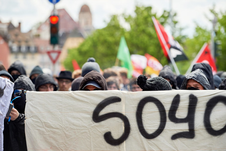 labor union: STRASBOURG, FRANCE - MAY 19, 2016: Group of youg people with covered faces holding placards walk with crowd during a demonstrations against proposed French governments labor and employment law reform