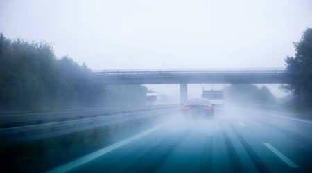 autobahn: Highway traffic on a rainy day on German European autobahn with cars driving over 200 kmh Stock Photo