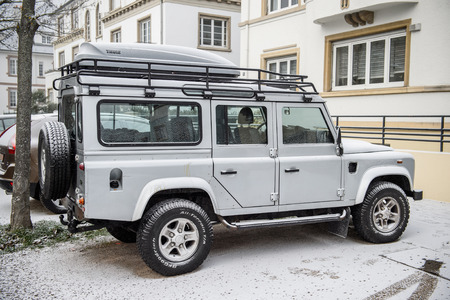 famous industries: PARIS, FRANCE - JAn 20, 2016: Side view of a Land Rover all terrain vehicle car coverd with snow on a winter morning