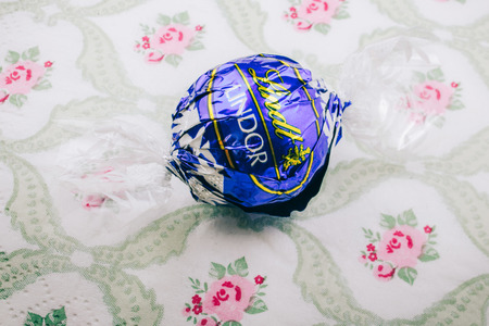 lindt: KILCHBERG, SWITZERLAND - MARCH 20, 2014: Lindt Lindor chocolate truffle on a luxury silk background. Lindt is one one of the lastgest luxury chocolate and confectionery company worldwide Editorial