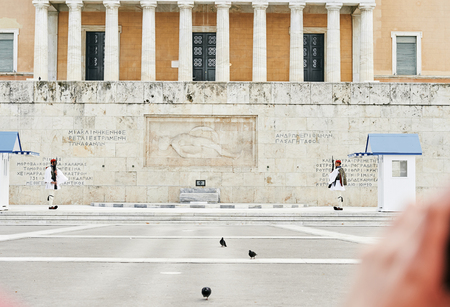 syntagma: Athens, Greece - March 27, 2016: The changing of the honor Evzones guards ceremony in front of  the Tomb of the Unknown Soldier at the Parliament Building in Syntagma Square, Athens, Greece.