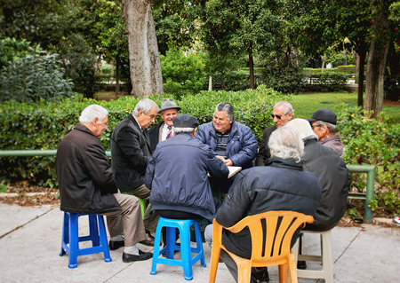 Athens, Greece - March 27, 2016: Old friends playing cards and laughing in National Garden park,the center of the Greek capital, Athens behind the Greek Parliament building