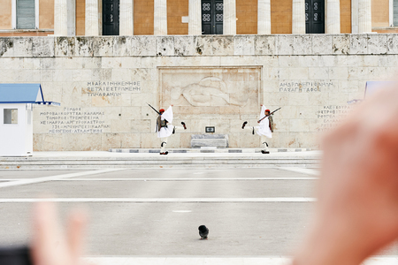 tomb of the unknown soldier: Athens, Greece - March 27, 2016: Perfect the coordination of movements during the changing of the honor Evzones guards ceremony in front of  the Tomb of the Unknown Soldier at the Parliament Building in Syntagma Square, Athens, Greece.
