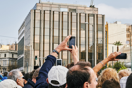 syntagma: Athens, Greece - March 27, 2016: Crowd admiring and photographing the changing of the honor Evzones guards ceremony in front of  the Tomb of the Unknown Soldier at the Parliament Building in Syntagma Square, Athens, Greece.