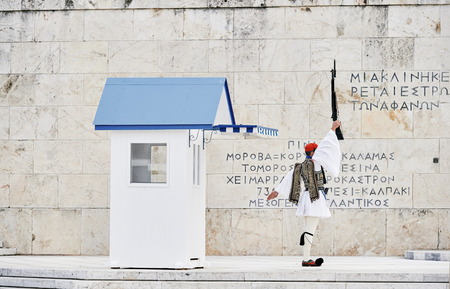 tomb unknown soldier: Honor Evzones guard woth rised rifle in front of  the Tomb of the Unknown Soldier at the Parliament Building in Syntagma Square, Athens, Greece.