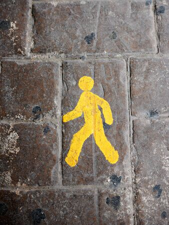 yeloow: Yellow pedestrian lane sign on a cobblestone road