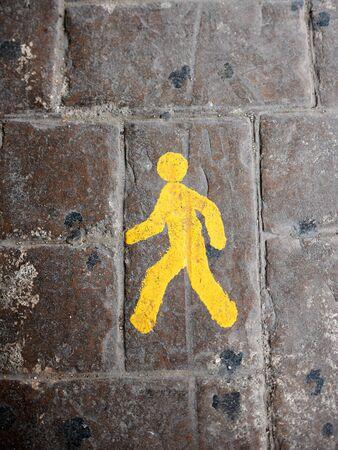 yeloow: Yellow pedestrian lane sign on a cobblestone road