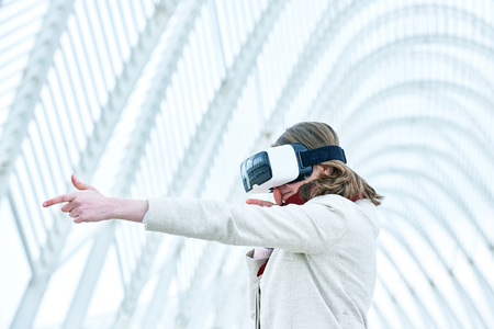 breaking new ground: Woman wearing a virtual reality headset, controlling the experience with hand gesture - immitating shooting from the gun