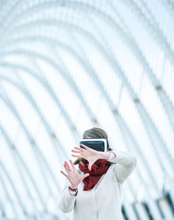 controling: Woman wearing a virtual reality headset, controlling the experience with hand gesture - touching and controling immaginare surfaces