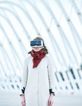 breaking new ground: Woman wearing a virtual reality headset standing in futuristic building space