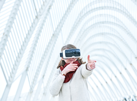 virtual reality simulator: Woman wearing a virtual reality headset, controlling the experience with hand gesture - immitating shooting from the gun