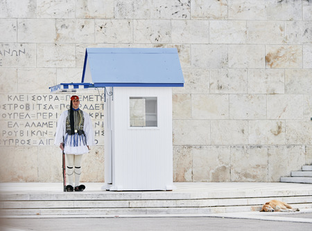 Athens, Greece - March 27, 2016: Still honor Evzones guards ceremony in front of  the Tomb of the Unknown Soldier at the Parliament Building in Syntagma Square, Athens, Greece. Редакционное
