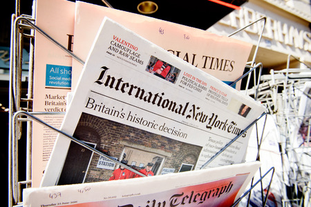 new york times: STRASBOURG, FRANCE - JUN 24, 2016: International New York Times and other major newspapers headline titles at press kiosk about the Brexit referendum in United Kingdom which has decidedthe country wishes to quit the European Union Editorial