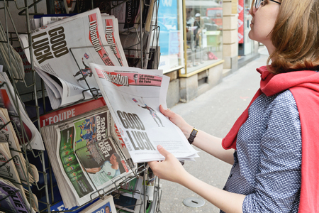 insecurity: STRASBOURG, FRANCE - JUN 25, 2016: Woman buying LIBERATION newspaper with shocking headline title at kiosk after the Brexit referendum in United Kingdom requesting to quit the European Union Editorial