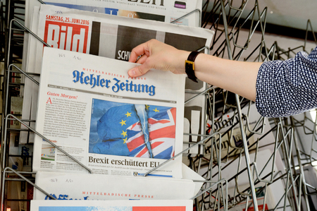 skepticism: STRASBOURG, FRANCE - JUN 25, 2016: Woman buying Kehler Zeitung newspaper with shocking headline titles at press kiosk about the Brexit referendum in United Kingdom requesting to quit the European Union Editorial