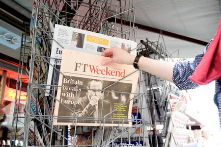skepticism: STRASBOURG, FRANCE - JUN 25, 2016: Woman buying Financial Times newspaper with shocking James Cameron PM headline titles at press kiosk about the Brexit referendum in United Kingdom requesting to quit the European Union