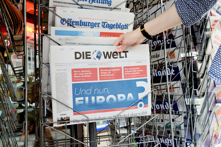 skepticism: STRASBOURG, FRANCE - JUN 25, 2016: Woman buying Die Welt newspaper with shocking headline titles at press kiosk about the Brexit referendum in United Kingdom requesting to quit the European Union