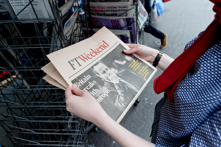pm: STRASBOURG, FRANCE - JUN 25, 2016: Woman buying Financial Times newspaper with shocking James Cameron PM headline titles at press kiosk about the Brexit referendum in United Kingdom requesting to quit the European Union