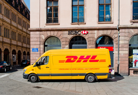 STRASBOURG, CIRCA 2016: DHL delivery van leaving after distributing parcels with HSBC bank branch behind in the center of the city
