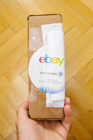 ebay: PARIS, FRANCE - JUN 8, 2016: Man hoding Ebay and Pitney Bowens box logotype printed on cardboard box security scotch tape of International Shipping Program. Editorial