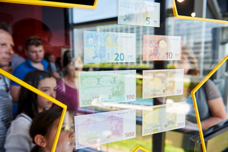 billets euro: STRASBOURG, FRANCE - MAY 8, 2016: People admiring all European Union Euro notes with a beautiful reflection of the window and European Parliament in the stars holding them �ditoriale