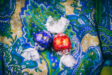 lindt: KILCHBERG, SWITZERLAND - MARCH 20, 2014: Two tasty Lindt Lindor chocolate truffle on a red luxury silk background.