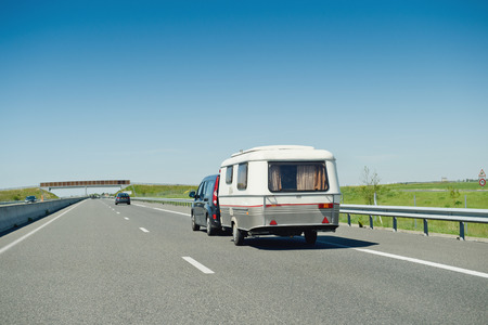RV van and trailer driving fast to vacance destination on highwayon a summer day Standard-Bild