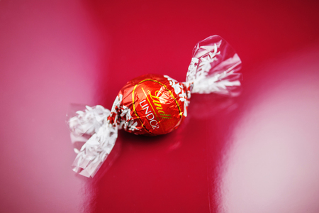 KILCHBERG, SWITZERLAND - MARCH 20, 2014: Lindt Lindor chocolate truffle on a red luxury silk background. Lindt is one one of the lastgest luxury chocolate and confectionery company worldwide with more than 30 factories worldwide