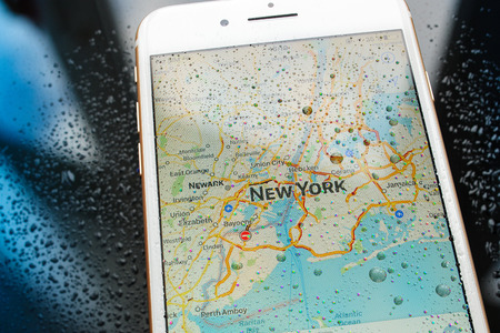 new york map: PARIS, FRANCE - SEP 26, 2016: New Apple iPhone 7 Plus unboxing and testing - New York map on smartphone under rain. New iPhone7 is one of the best waterproof smart phone in the world