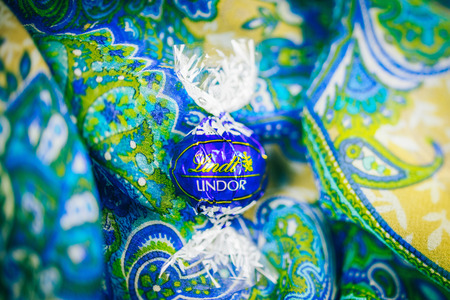 KILCHBERG, SWITZERLAND - MARCH 20, 2014: Lindt Lindor chocolate truffle on a red luxury blue floral background. Lindt is one one of the lastgest luxury chocolate and confectionery company worldwide with more than 30 factories worldwide Editorial