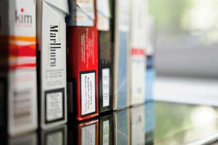 FRANKFURT, GERMANY - SEP 22, 2012: Row of packs of cigarettes from diverse corners of the world with all indications of nicotine mass Editorial