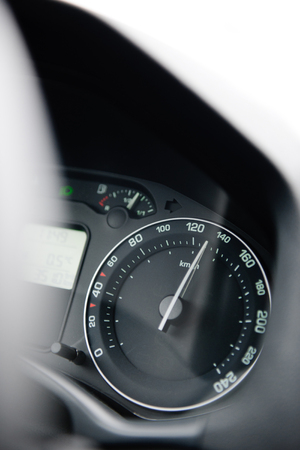 Car speedometer close-up with the needle pointing a high 130 kmmph speed, blur effect and blue tone to depict high speed concet and security driving electric car