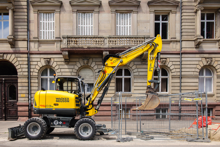 compact track loader: STRASBOURG, FRANCE - MAY 18, 2016: Wacker Neuson Yellow excavator working in urban environment  with luxury apartment office historic building behind