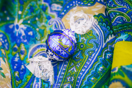 KILCHBERG, SWITZERLAND - MAR 20, 2014: Tasty blue Lindt Lindor chocolate on a colored silk background, Lindt AG, more commonly known as Lindt, is a Swiss chocolatier and confectionery company founded in 1845 and known for their chocolate truffle balls and